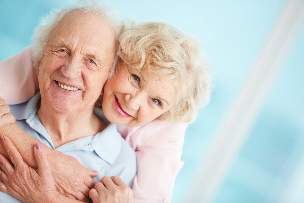 Happy And Affectionate Elderly Couple Looking At Camera