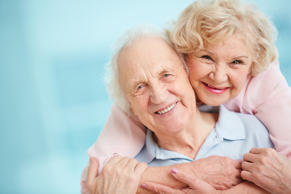 Happy And Affectionate Elderly Couple Looking At Camera With Smiles