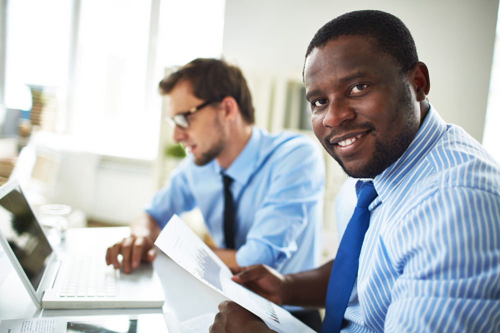 Image Of Happy Young Businessmen Looking At Camera On Background Of His Colleague Using Laptop