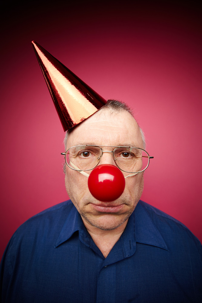 Portrait Of Unhappy Man With A Red Nose And In A Cone Cap On Fool