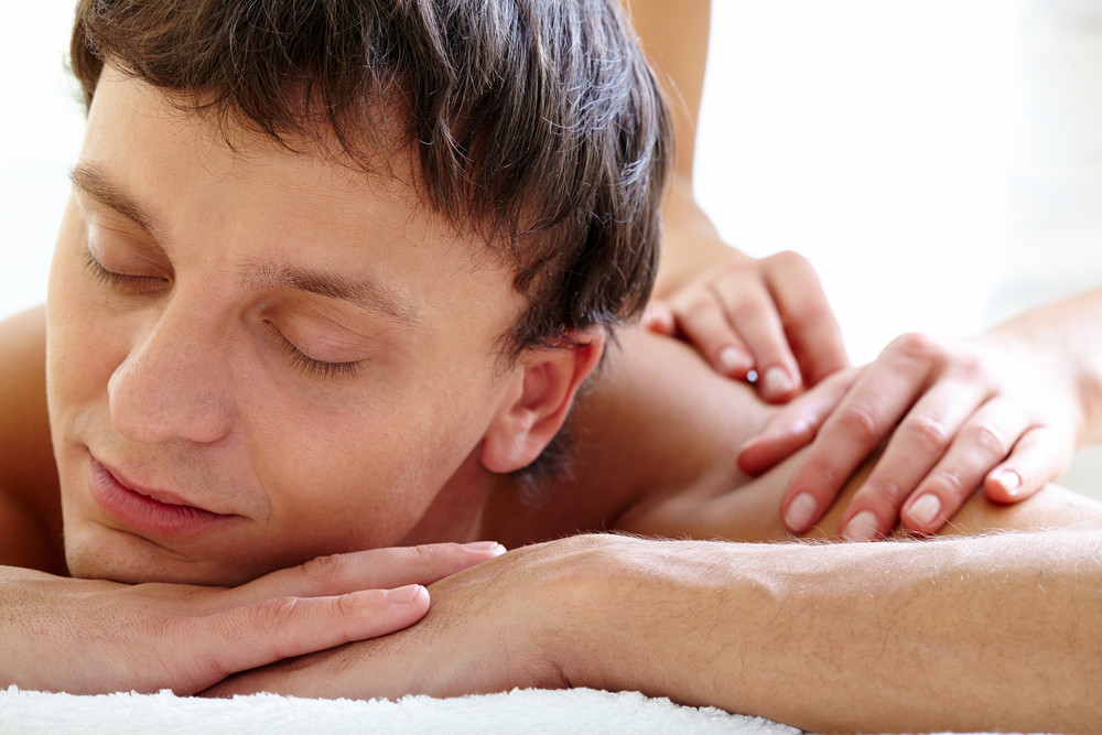 Portrait Of Young Man Enjoying The Procedure Of Massage In Spa Salon