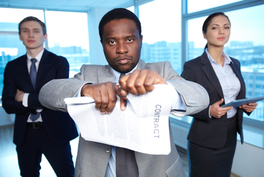 Portrait Of African Businessman Tearing Contract While Looking At Camera With Two Partners On Background