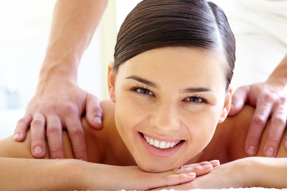 Smiling Female Looking At Camera During Massage