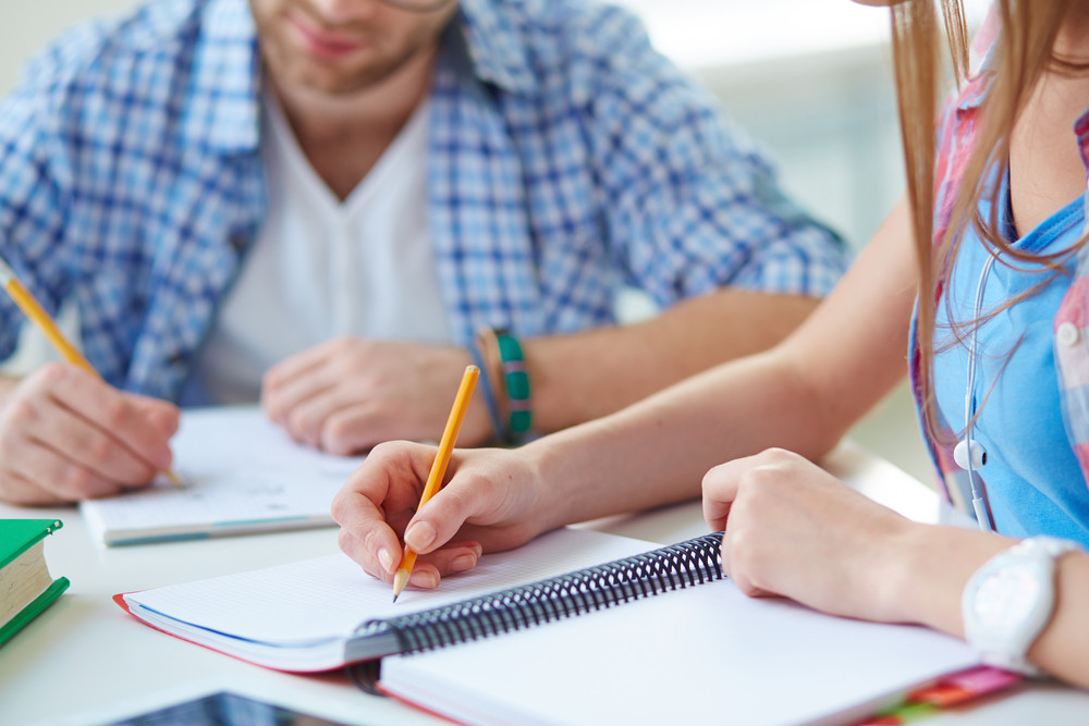 Hand Of Student With Pencil Making Notes In Exercise-book In Working Environment