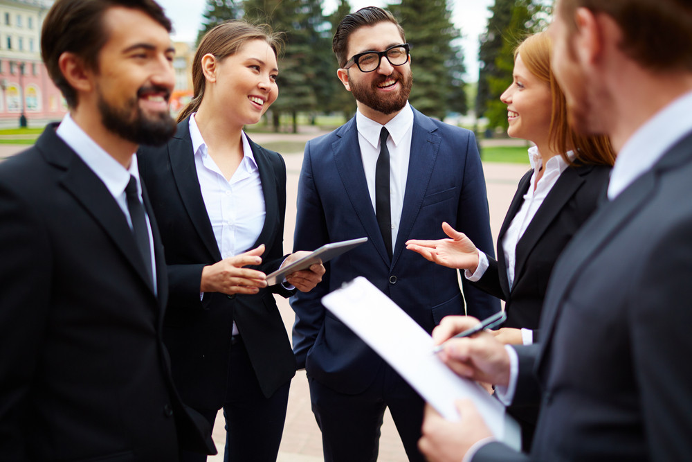 Group Of Business People Talking At Meeting Outside