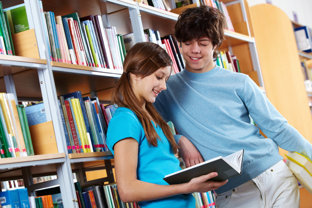 Two Cheerful Students Reading A Book Together At Library