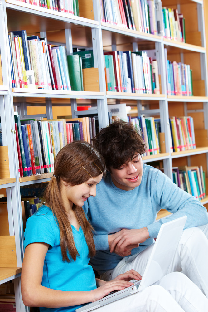 Two Schoolkids Studying At Library With The Use Of Modern Technologies