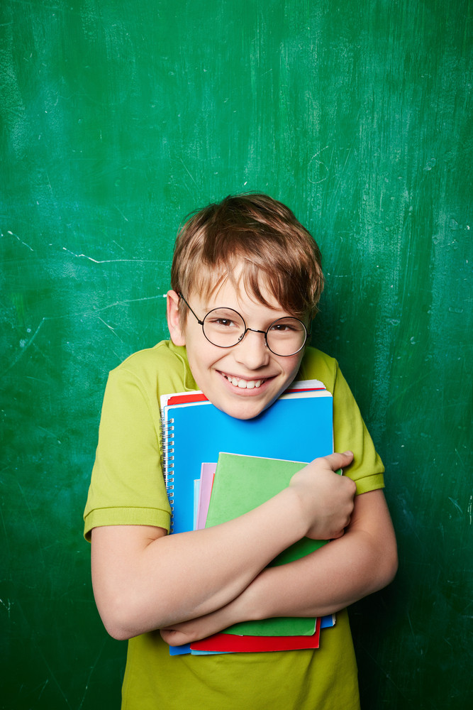 Portrait Of Smiling Schoolboy In Eyeglasses Looking At Camera By The Blackboard