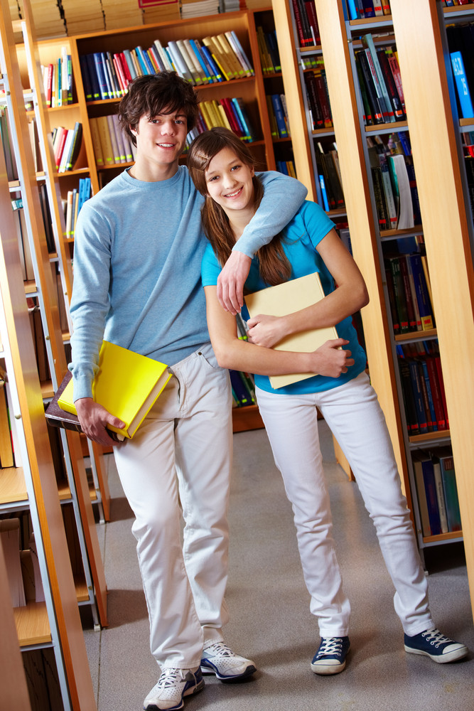 Tilt Up Shot Of Teenage Couple Standing Together At Library And Smiling At Camera