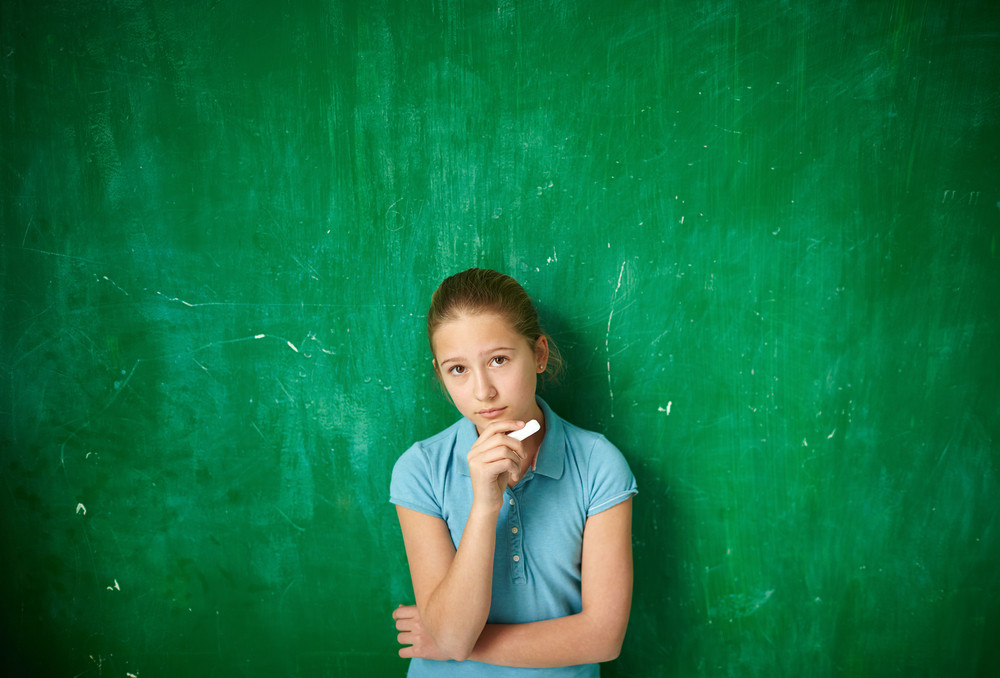 Portrait Of Cute Schoolgirl With Piece Of Chalk Looking At Camera By The Blackboard