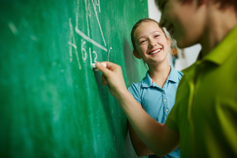 Happy Girl Looking At Her Classmate By The Blackboard At Geometry Lesson
