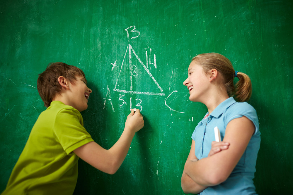 Portrait Of Two Joyful Classmates By The Blackboard At The Lesson Of Geometry