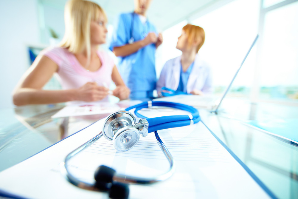 Close-up Of Stethoscope And Document On Background Of Doctors And Patient Communicating