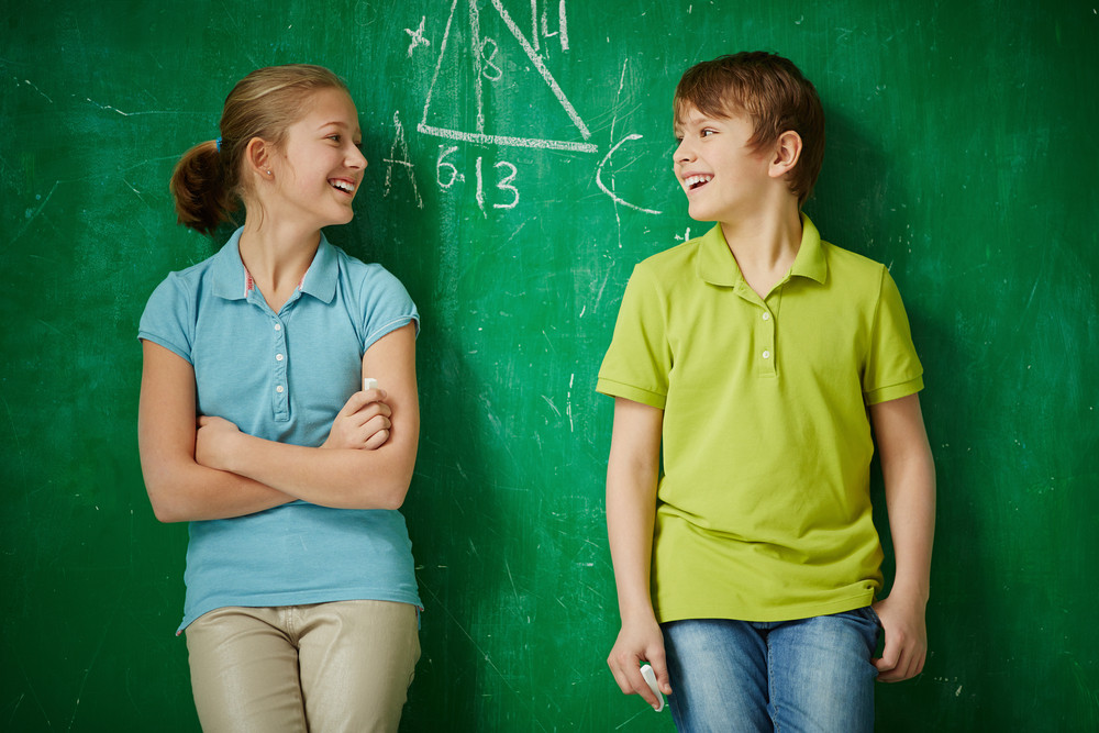 Portrait Of Two Joyful Classmates Looking At One Another By The Blackboard