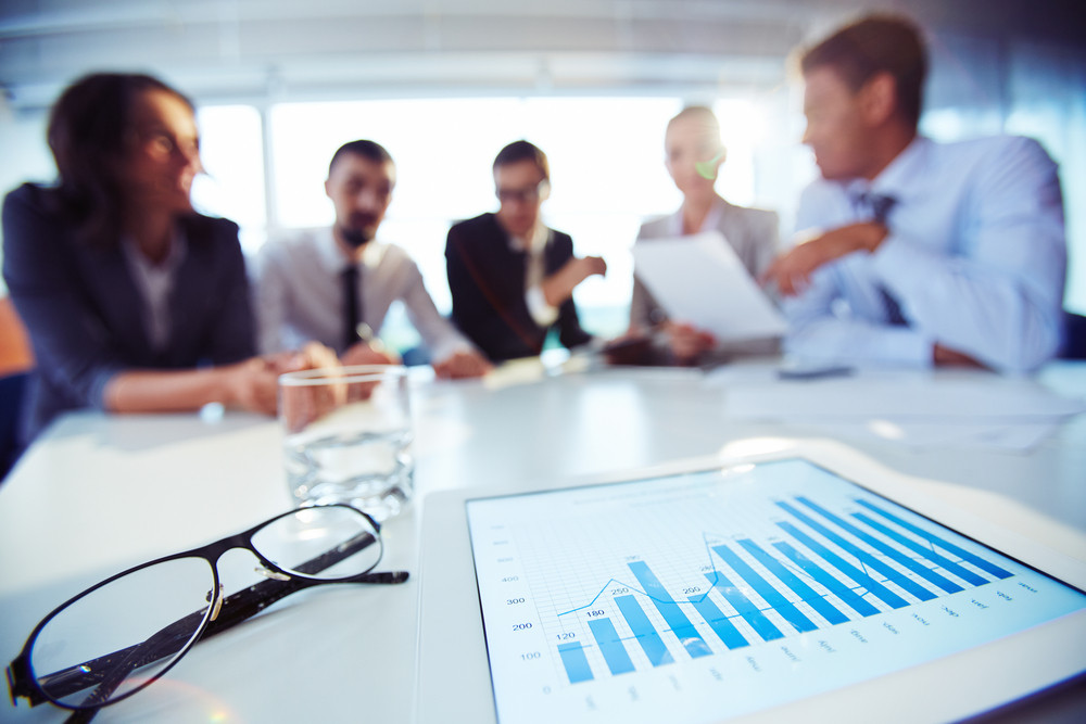 Paper With Chart And Eyeglasses On Background Of Business Colleagues