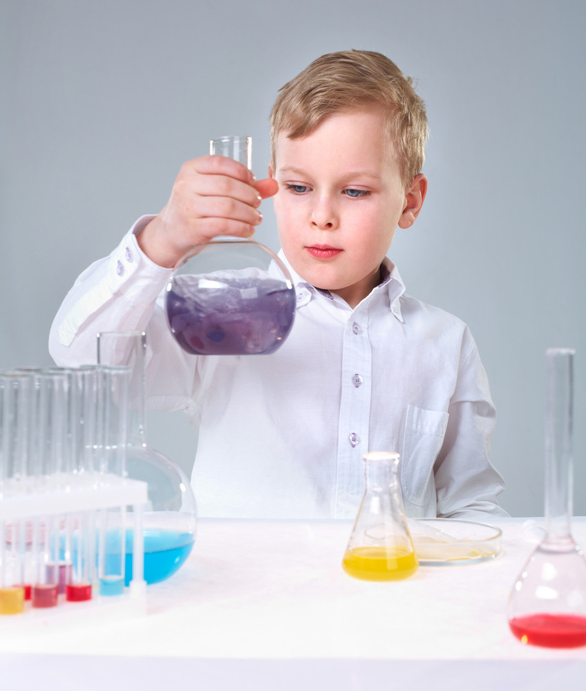 A Little Boy Looking At Liquid In Flask