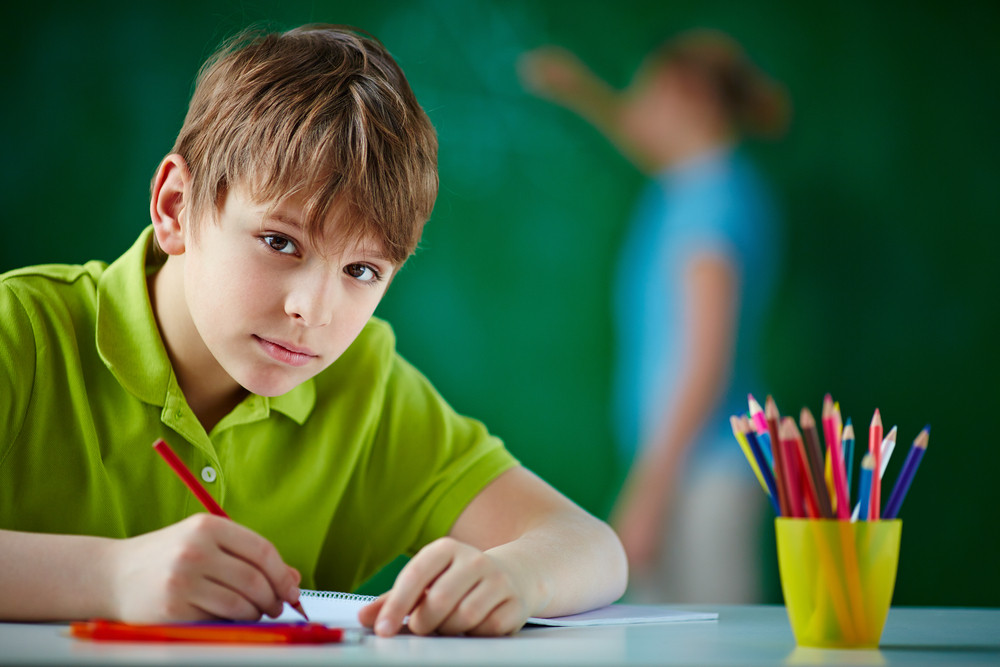 Portrait Of Cute Schoolboy Drawing With Colorful Pencils And Looking At Camera