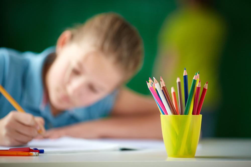 Image Of Multi-colored Pencils On Background Of Girl Drawing