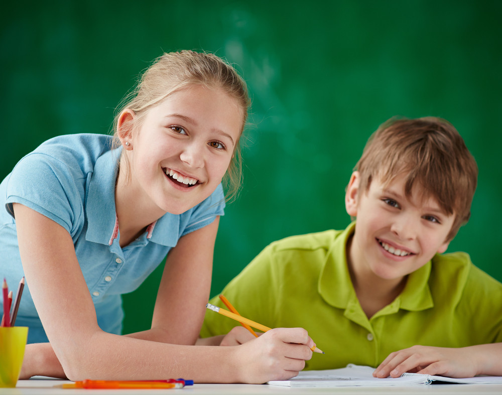 Portrait Of Cute Schoolkids Looking At Camera While Drawing At Lesson