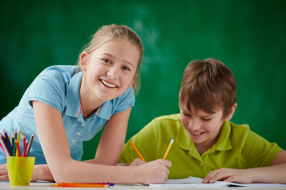 Portrait Of Cute Schoolgirl Looking At Camera While Drawing At Lesson With Classmate Near By