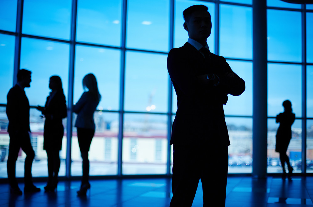 Outlines Of Business Team Standing Against Window With Leader In Front