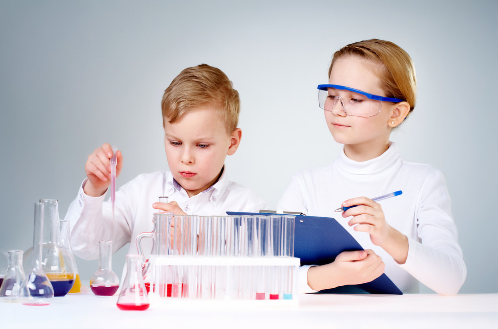 A Little Boy Mixing Chemical Liquids And His Assistant Making Notes