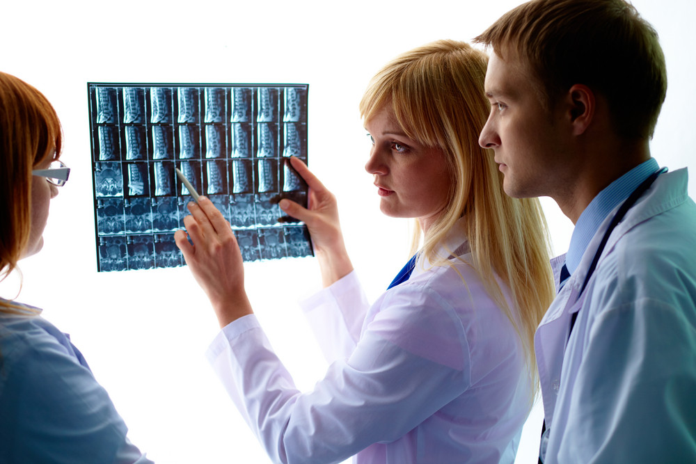 Young Female Doctor Showing And Interpreting X-ray To Colleagues