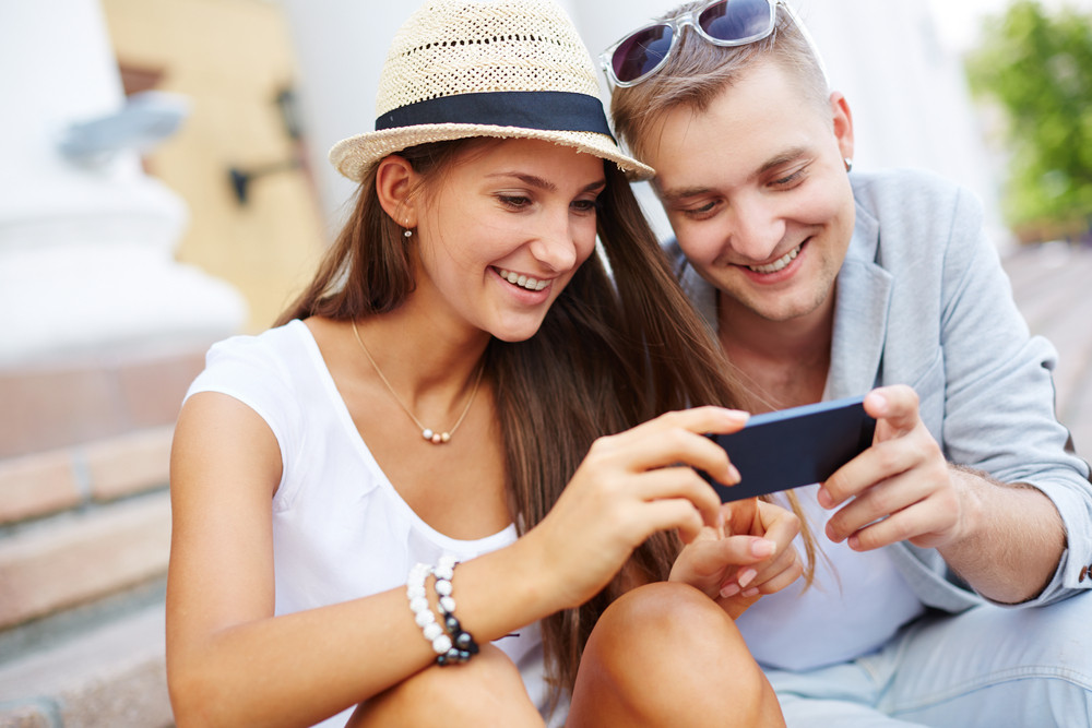 Happy Girl And Her Boyfriend Using Mobile Phone Outside