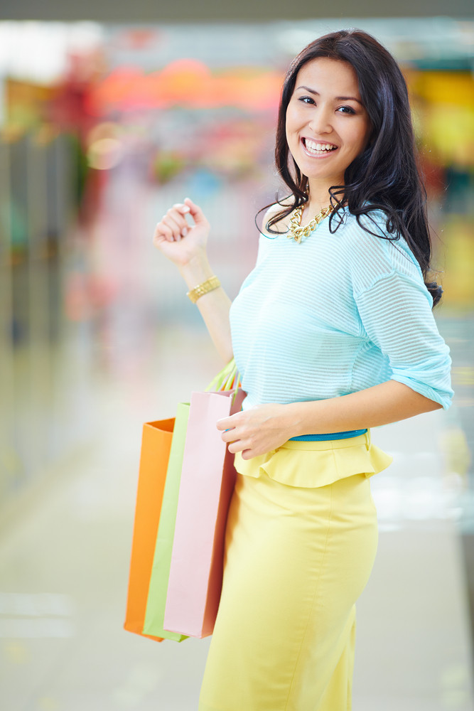 Portrait Of Happy Girl Holding Colorful Shopping Bags