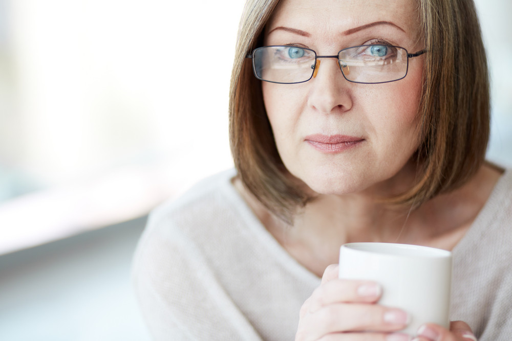 Portrait Of Mature Woman With Cup Looking At Camera