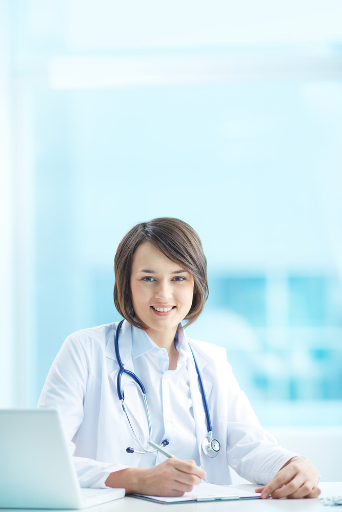 Vertical Portrait Of A Young Female Doctor Looking At Camera At Her Workplace