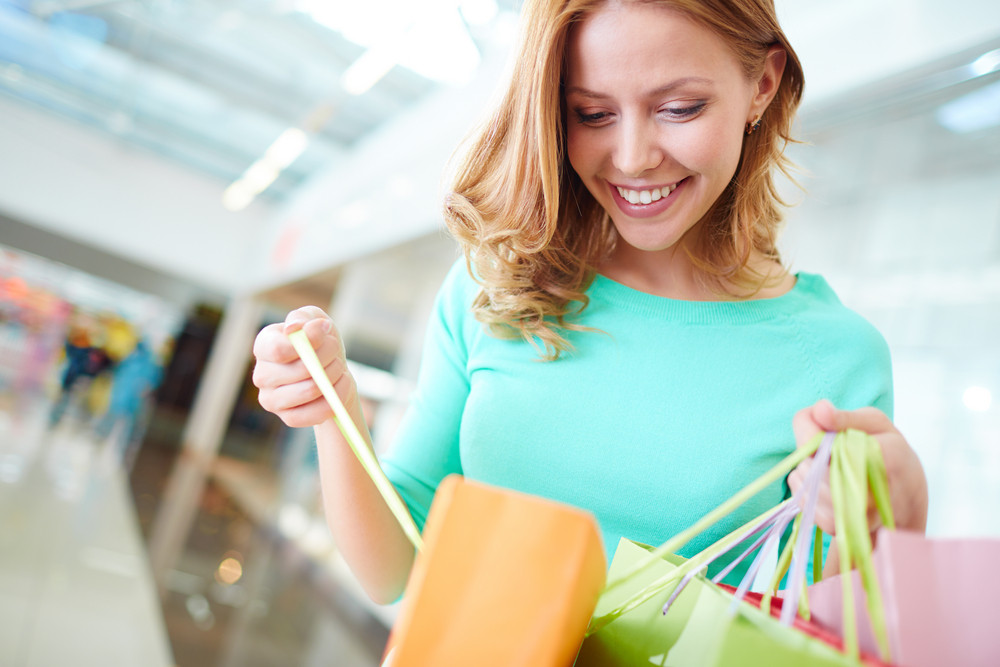Portrait Of Happy Girl With Shopping Bags Looking Into One Of Them