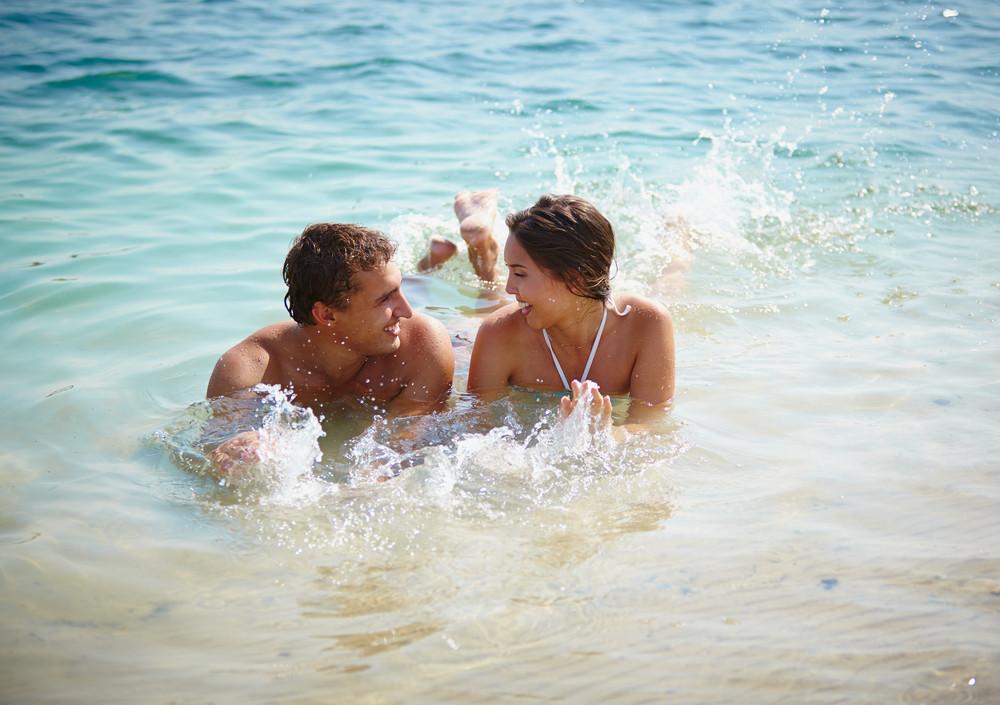 Cheerful Couple Splashing In Water At Resort