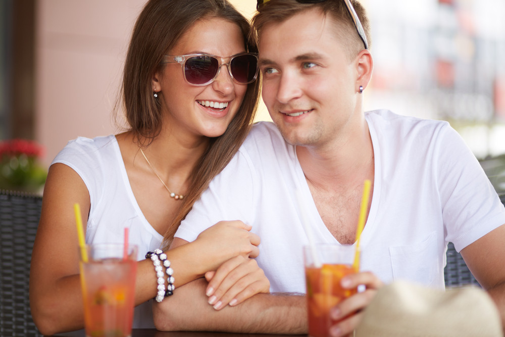 Young Guy And His Girlfriend Sitting In Cafe On Summer Day