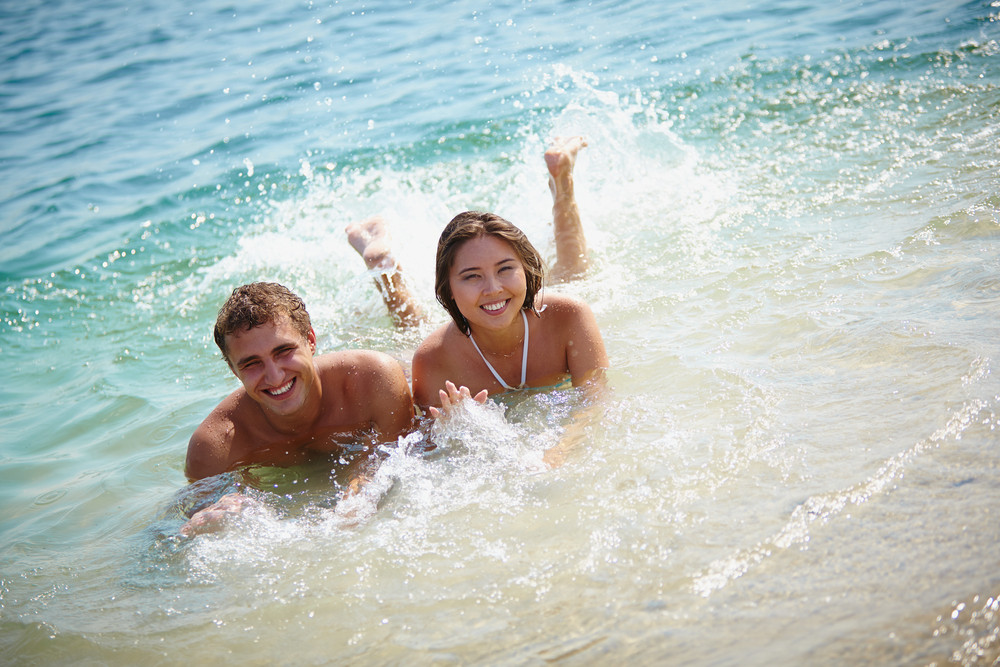 Cheerful Couple Relaxing In Water At Resort And Looking At Camera