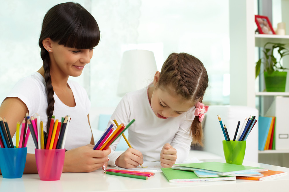 Portrait Of Cute Girl Drawing With Colorful Pencils With Her Mother Near By