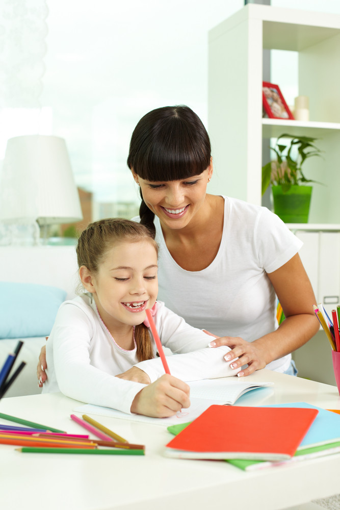 Portrait Of Happy Girl Drawing With Colorful Pencils With Her Mother Near By