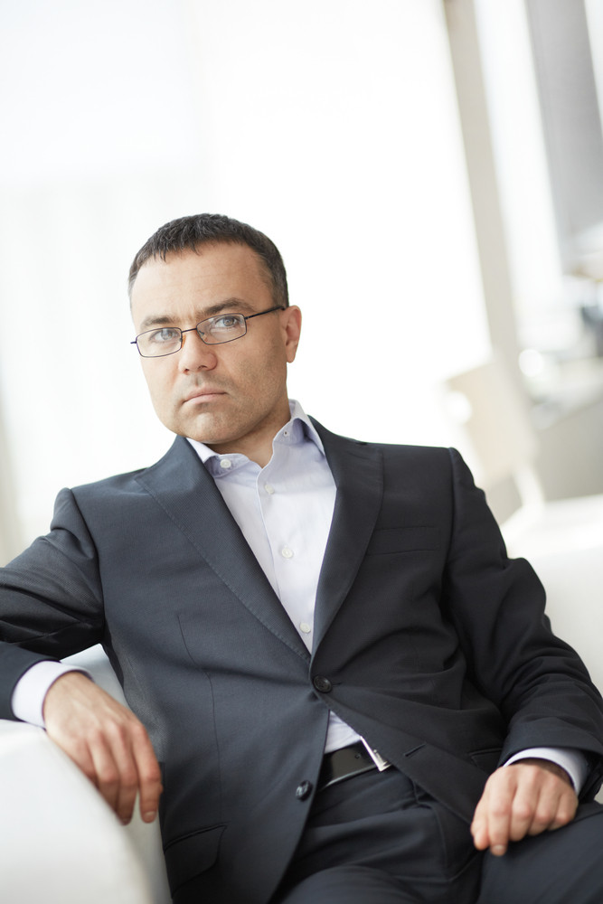 Portrait Of Elegant Businessman Sitting In Office And Looking At Camera