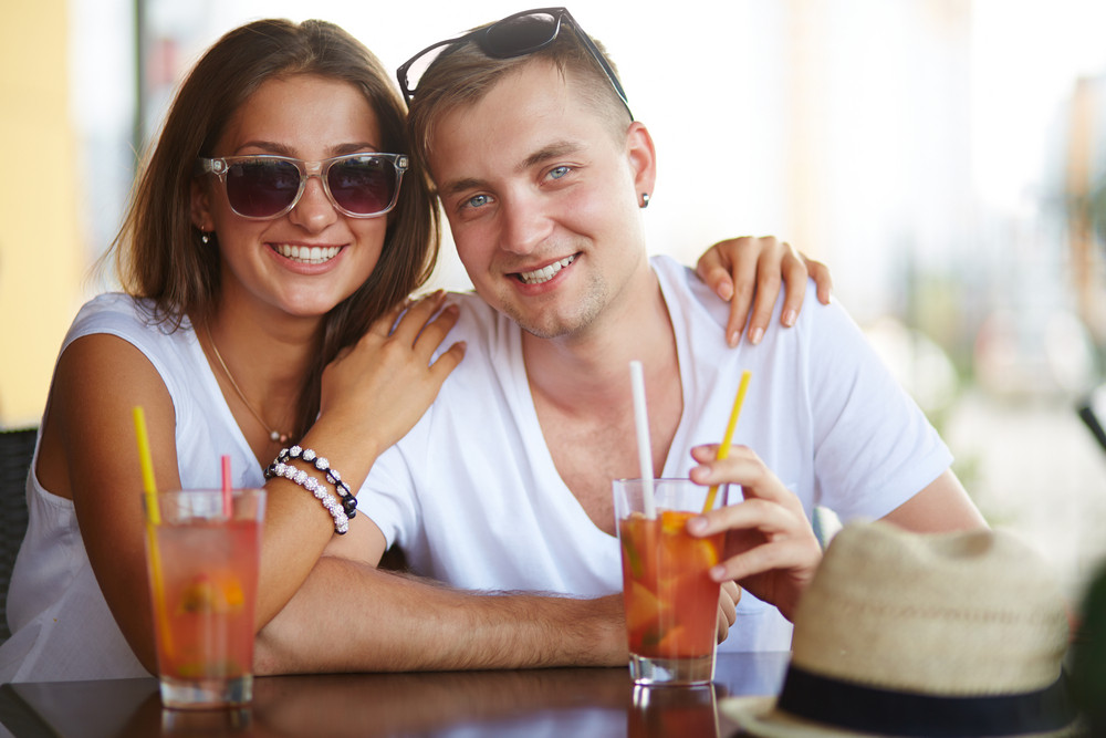 Young Couple Sitting In Cafe On Summer Day And Looking At Camera