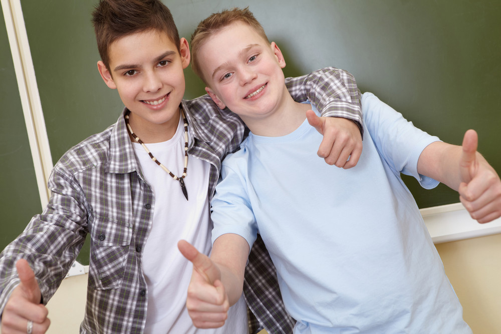 Portrait Of Smart Teenage Guys Showing Thumbs Up While Looking At Camera