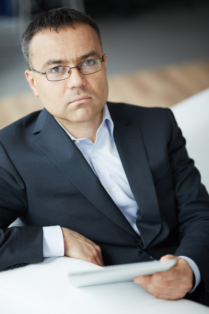 Portrait Of Elegant Businessman Sitting In Office