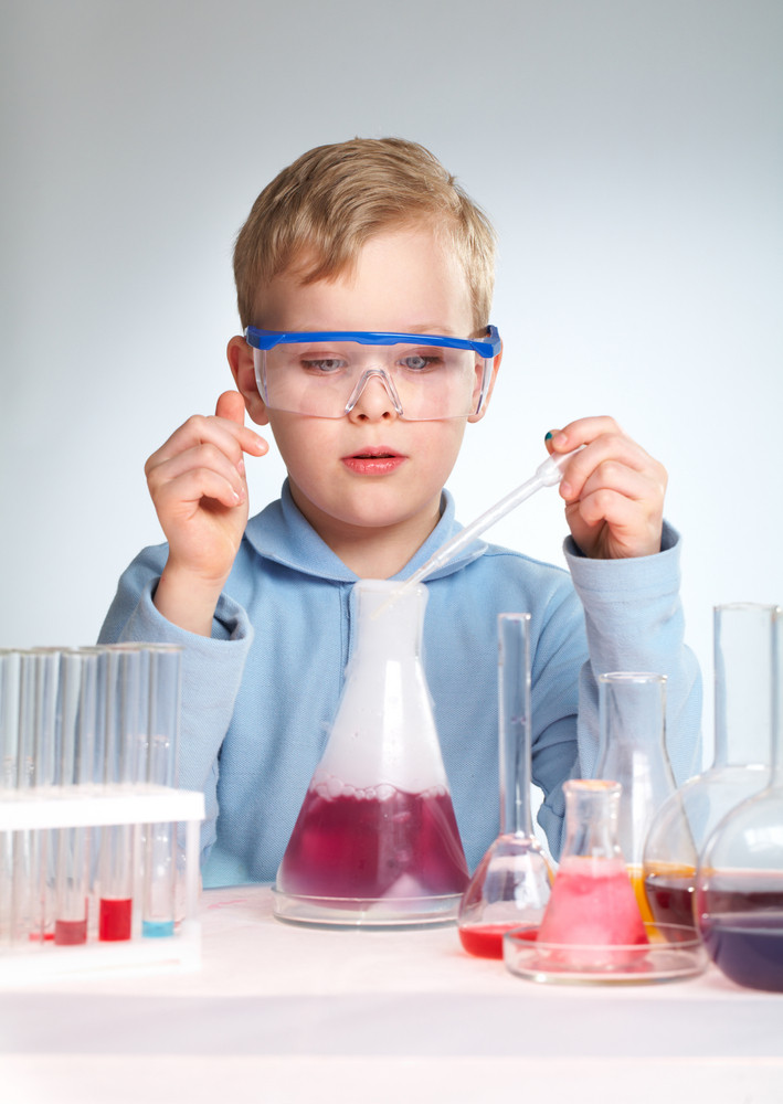 Vertical Shot Of A School Scientist Being Curious About Chemical Reaction