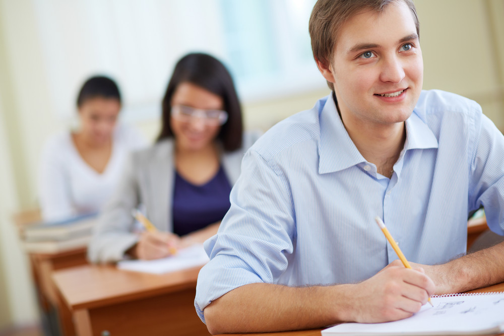 Portrait Of Handsome Student Listening To The Teacher On Background Of Two Girls