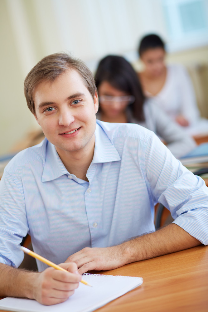 Portrait Of Handsome Student Looking At Camera At Lesson On Background Of Two Girls