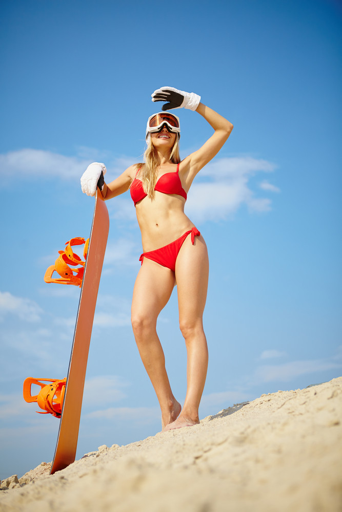 Slim Girl Posing With Snowboard On The Beach Waiting For Winter Season
