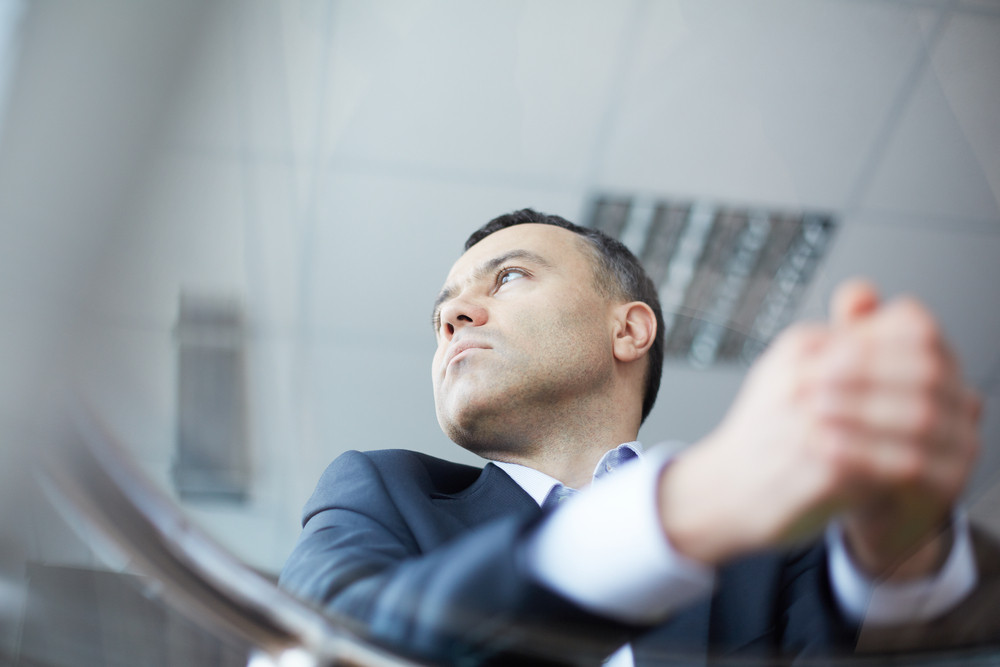 Close-up Of Pensive Businessman Face Viewed Through Glass Table