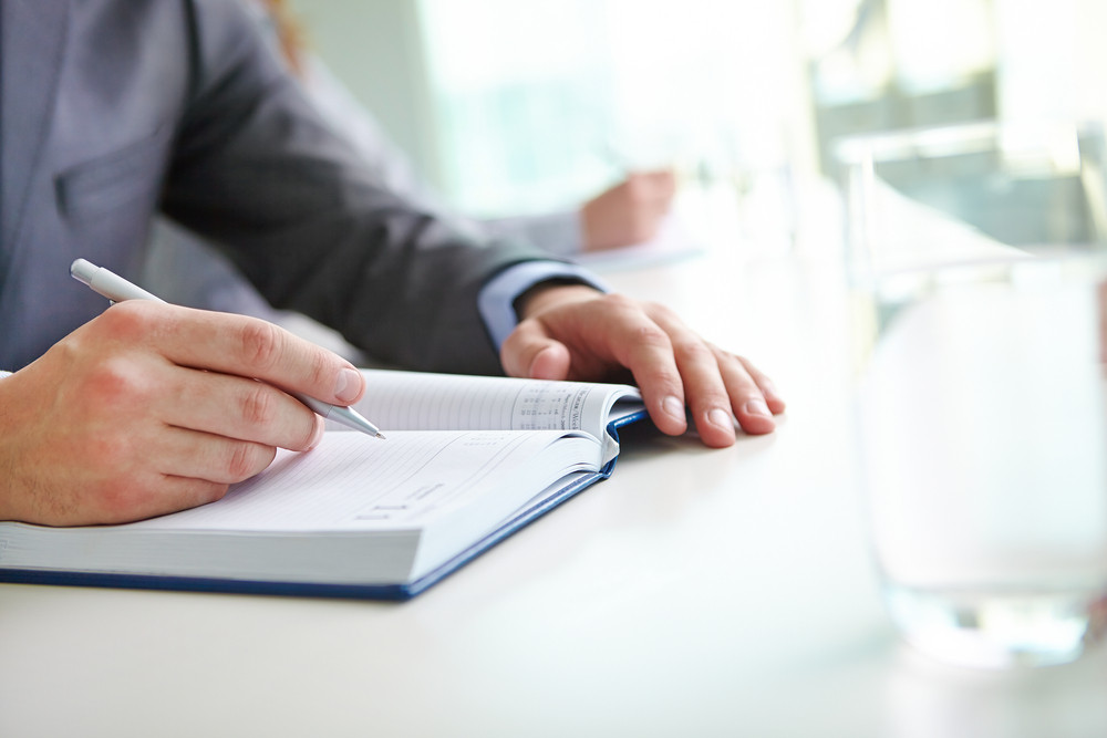 Hand Of Businessman With Pen Writing In Notebook At Seminar