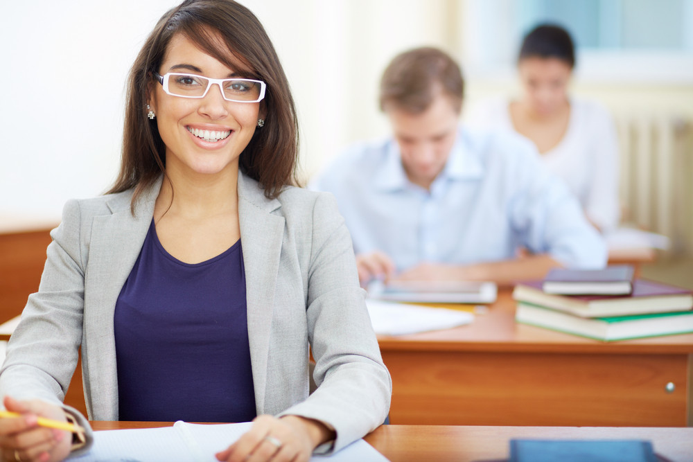 Portrait Of Female Student Looking At Camera At Lesson On Background Of Two Group Mates