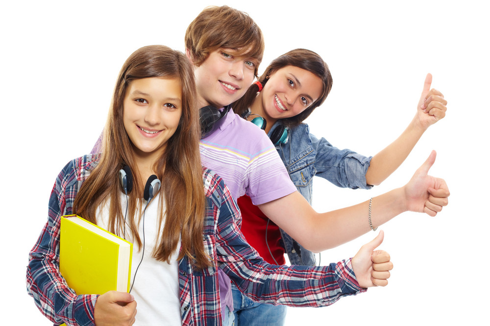 Row Of Teens With Headphones Showing Thumbs Up And Smiling At Camera