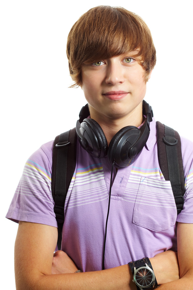Portrait Of Teenage Boy With Headphones And Backpack Looking At Camera